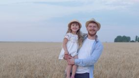Portrait of happy daddy with kid girl, young man stays with cheerful smiling daughter on his hands looking at each other. In grain wheat golden field at crop stock footage