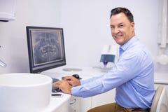 Portrait of happy dentist examining x-ray report on computer stock photo