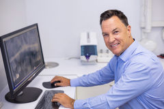 Portrait of happy dentist examining x-ray report on computer Stock Image