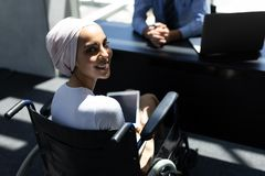 Disabled mixed-race female executive holding digital tablet in modern office royalty free stock photography