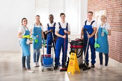 Portrait Of Diverse Janitors. Portrait Of Happy Diverse Janitors In The Office With Cleaning Equipments stock image