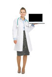 Portrait of happy doctor woman showing laptop blank screen. Full length portrait of happy doctor woman showing laptop blank screen isolated on white Stock Photos