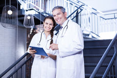 Portrait of happy doctors holding digital tablet on staircase royalty free stock photography