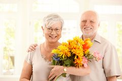 Portrait of happy elderly couple with flowers. Woman holding bouquet, smiling at camera Stock Images
