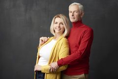 Portrait of a beautiful senior couple. Portrait of a happy elderly couple standing together at isolated dark background Stock Image