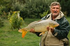 Portrait of a fisherman standing with a fish. royalty free stock photo