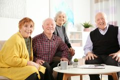Portrait of happy elderly people at table stock photography