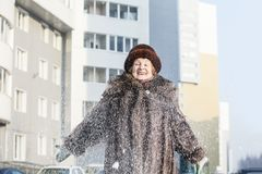Portrait of happy elderly woman in fur coat and hat on city street in snowy winter