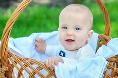 Portrait of a happy elegant blond infant in white suit with bow tie sitting in a basket on a spring or summer picnic stock images