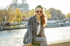 Portrait of happy elegant woman sitting on the parapet n Paris Royalty Free Stock Photography
