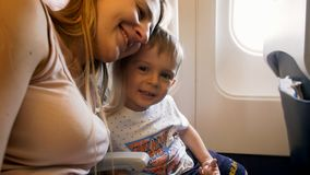 Portrait of happy embracing mother with little son sitting in passenger jet airplane. Portrait of embracing mother with little son sitting in passenger jet stock image