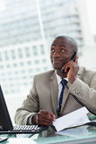 Portrait of a happy entrepreneur making a phone call while readi Stock Images