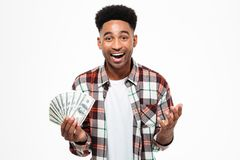 Portrait of a happy excited african man. Holding bunch of money banknotes and looking at camera isolated over white background Royalty Free Stock Photos