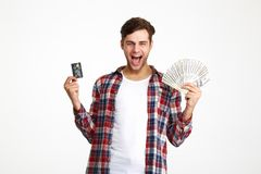 Portrait of a happy excited man. Holding bunch of money banknotes with a credit card and screaming isolated over white background Stock Image