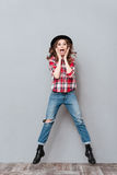 Portrait of a happy excited woman in plaid shirt jumping Stock Photo