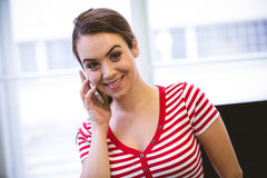 Portrait of happy executive listening to cellphone at office Royalty Free Stock Photos