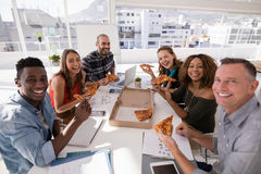 Portrait of happy executives having pizza. In office royalty free stock photography