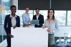 Portrait of happy executives holding a blank banner. In office royalty free stock photography