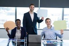 Portrait of happy executives holding speech bubble stock photography