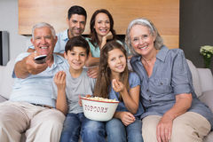Portrait of happy extended family watching tv in living room Stock Photo