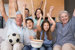 Portrait of happy extended family watching tv in living room Stock Photos
