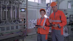 Portrait of happy factory workers men and female in helmets and overalls near conveyor line with tablets in hands during stock video footage