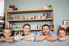 Portrait of happy family with arms crossed. Behind sofa in house Stock Photo