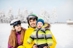 Happy family during the winter vacations. Portrait of a happy family with baby boy during the winter vacations on the beautiful snow-covered mountains royalty free stock photo