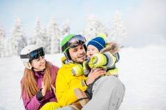 Happy family during the winter vacations. Portrait of a happy family with baby boy during the winter vacations on the beautiful snow-covered mountains royalty free stock images
