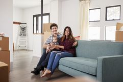 Portrait Of Happy Family With Baby Resting On Sofa Surrounded By Boxes In New Home On Moving Day stock photo