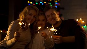 Portrait of happy family with bengal lights, celebrating Christmas together stock photo