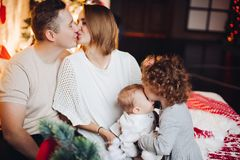 Kissing parents with hugging kids at Christmas. stock image