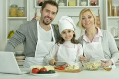 Portrait of happy family cooking in kitchen. With laptop royalty free stock photos