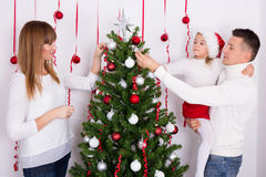 Portrait of happy family decorating Christmas tree Royalty Free Stock Photo