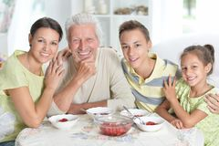 Portrait of happy family eating fresh strawberries stock photo