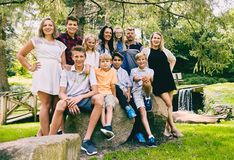 Happy family of eleven posing together in park. Portrait of happy family of eleven posing together in summer park. Mature couple with teen and preteen children royalty free stock photos