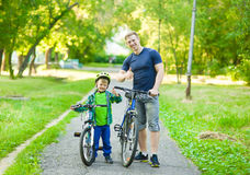 Portrait of a happy family - father and son bicycling in the park royalty free stock image