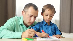 Portrait of a happy family. Father and son draw with colored markers, sitting at the table.