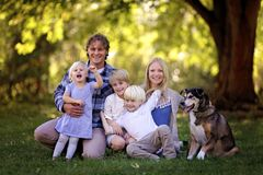 Portrait of Happy Family of Five Caucasian People and Their Pet. A portrait of a family of 5 blonde haired, caucasian people, sitting outside under the trees Royalty Free Stock Photo