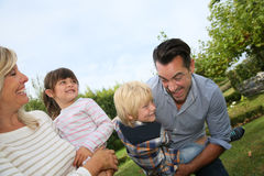 Portrait of happy family fooling around in the garden Stock Image