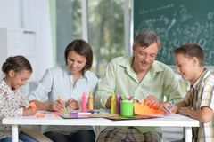 Portrait of happy family of four drawing together at home royalty free stock images