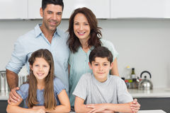 Portrait of a happy family of four in kitchen Stock Photo