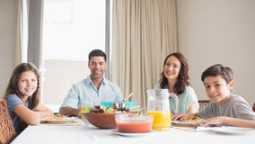 Portrait of happy family of four sitting at dining table Stock Photography