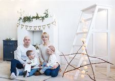 Portrait of happy family of four sitting on floor in white room at home Royalty Free Stock Photos