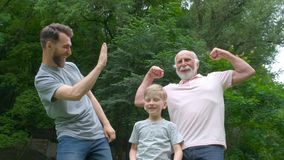 Portrait of happy family - grandpa, father and his son smiling and showing their muscles outdoor in park on background
