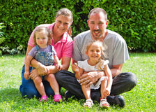 Portrait of happy family on the green lawn Stock Photo