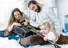 Portrait of happy family with a guitar against domestic festive backdrop. Portrait of happy family against domestic festive backdrop. The father holds a guitar Stock Photo