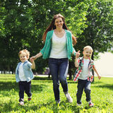 Portrait of happy family having fun together outdoors. At the weekend, mother and two children sons playing run through the grass in the park, enjoying summer Royalty Free Stock Photo