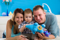 Portrait of happy family at home. Baby boy ( 1 year old ) and young parents father and mother sitting on floor and playing together at children's room, smiling royalty free stock photo