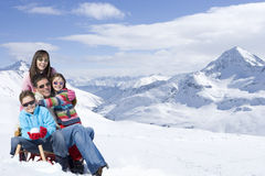 Portrait of happy family hugging on snowy mountain Royalty Free Stock Photo